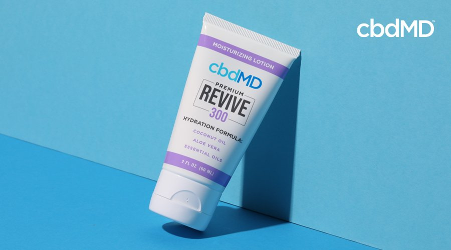 A 300 mg tube of cbd revive from cbdmd sits at an angle against a blue wall