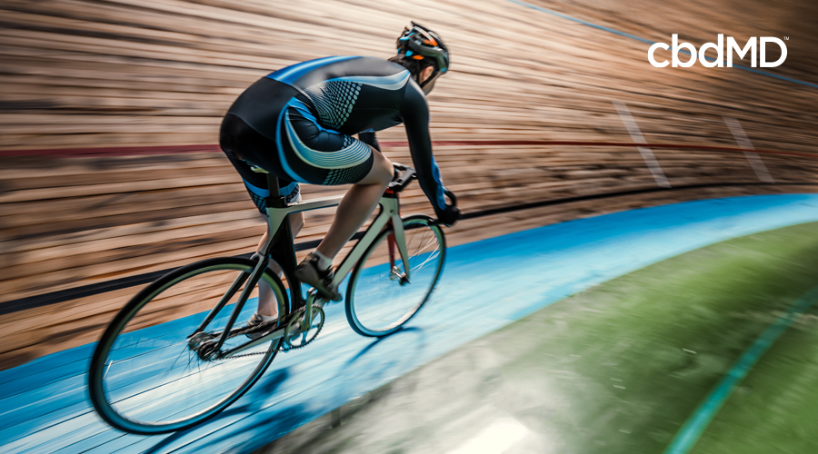 A cyclist in a blue and black outfit rides his road bike on an indoor track