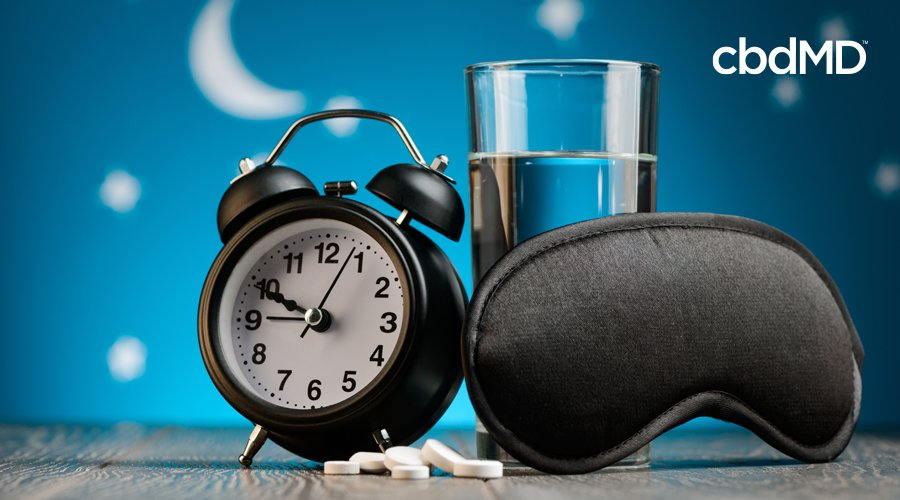 A black alarm clock, a sleep mask, and a glass of water sit on a table near a pile of pills