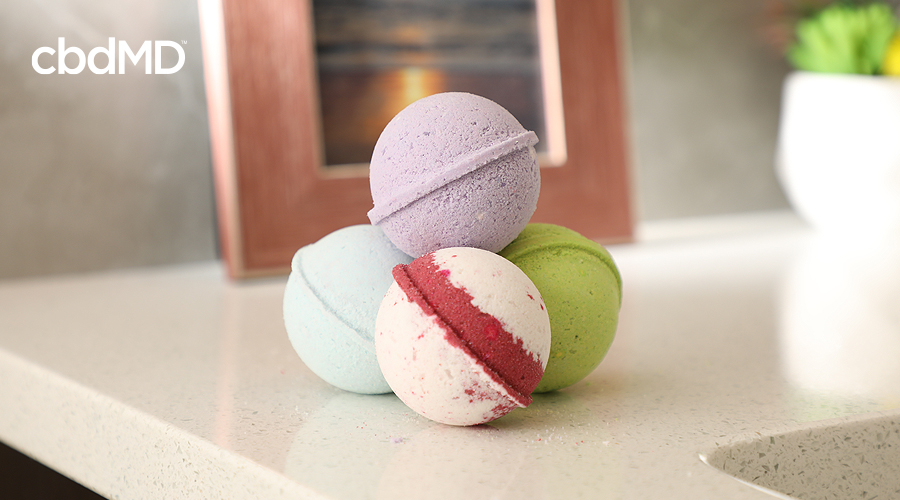 A small stack of cbd bath bombs from cbdmd sits on a bathroom counter