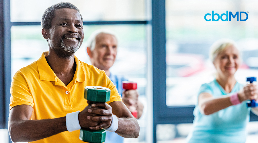 A group of older people hold weights as they workout and a dark skinned man with white hair stands in the front with a yellow shirt