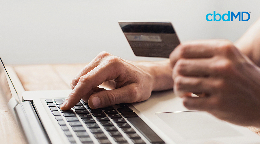 A computer sits on a desktop with someone making a purchase as they hold their credit card