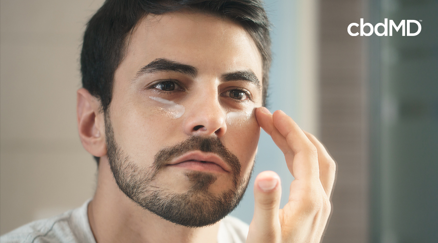 A young man with a beard puts cbd night cream from cbdmd on his face