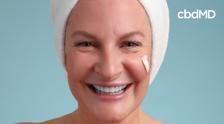 An older woman with cbd night cream from cbdmd on her face looks ahead with a towel on her head