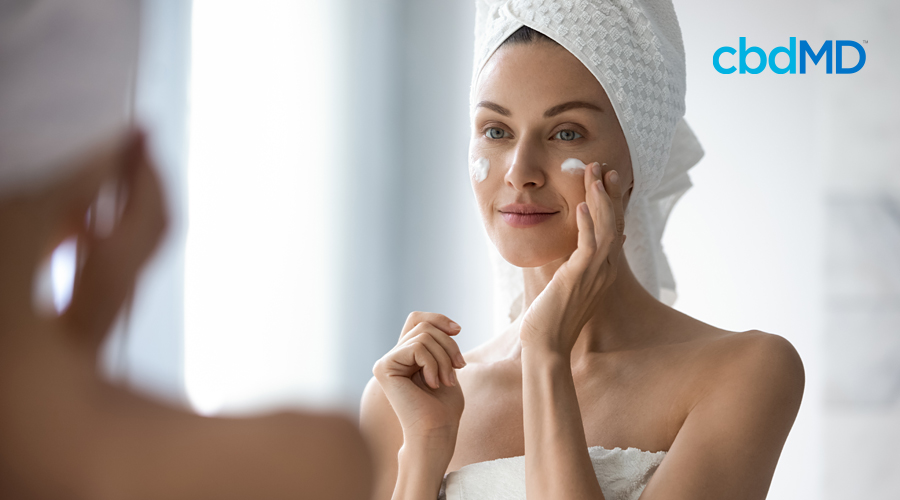 An attractive brunette puts cbd night cream from cbdmd on her face while looking in the mirror