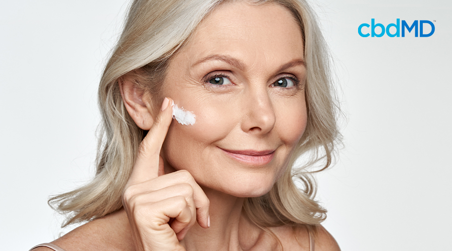 An older woman with greying hair rubs cbd night cream from cbdmd on her face
