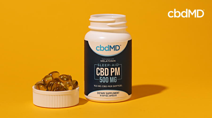 A bottle of 500 mg cbd pm softgell capsules sits next to a cap full of capsules