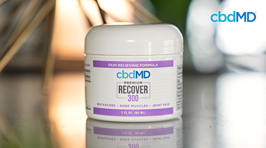 A jar of 300 mg cbd recover from cbdmd sits on a reflective surface