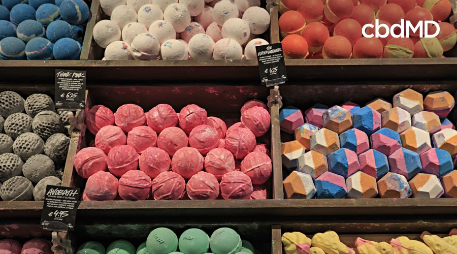 A large wooden display holds many bath bombs for sale