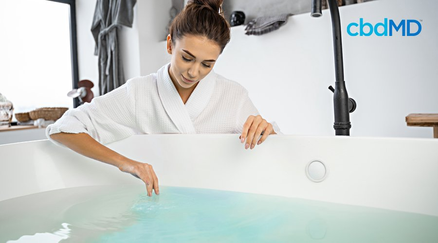 A woman in a white bath robe readies herself to get into the water that contains cbd bath bombs from cbdmd