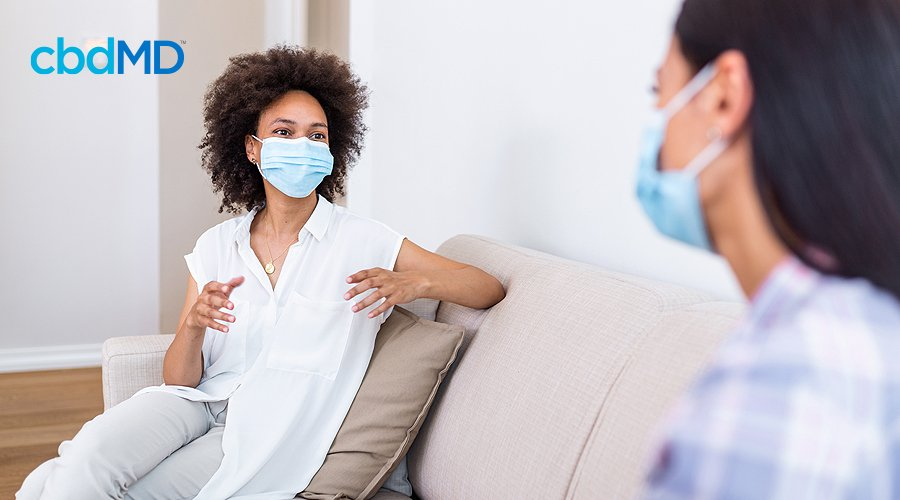 Two women sit on a couch in a well lit room and talk with each other while wearing medical masks