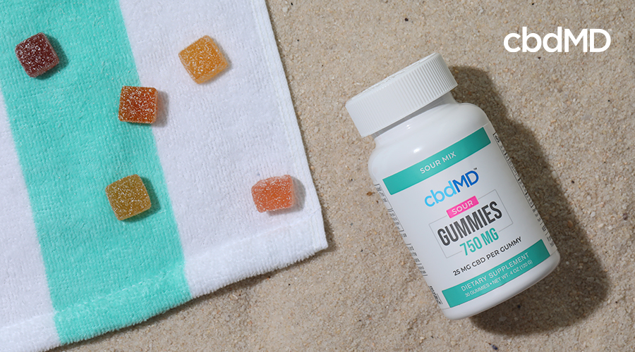 cbdMD sour gummy bottle and gummies laying on a towel.