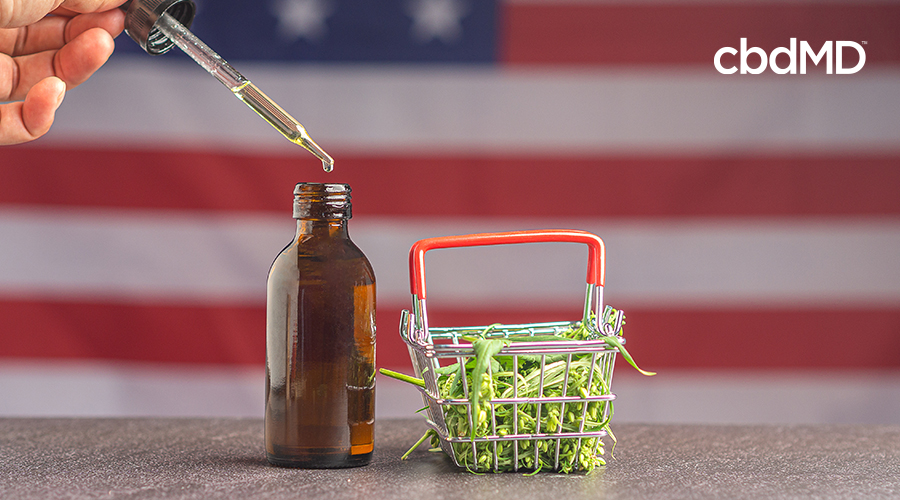 dropper going into tincture bottle with cannabis in shopping cart while usa flag is in the background