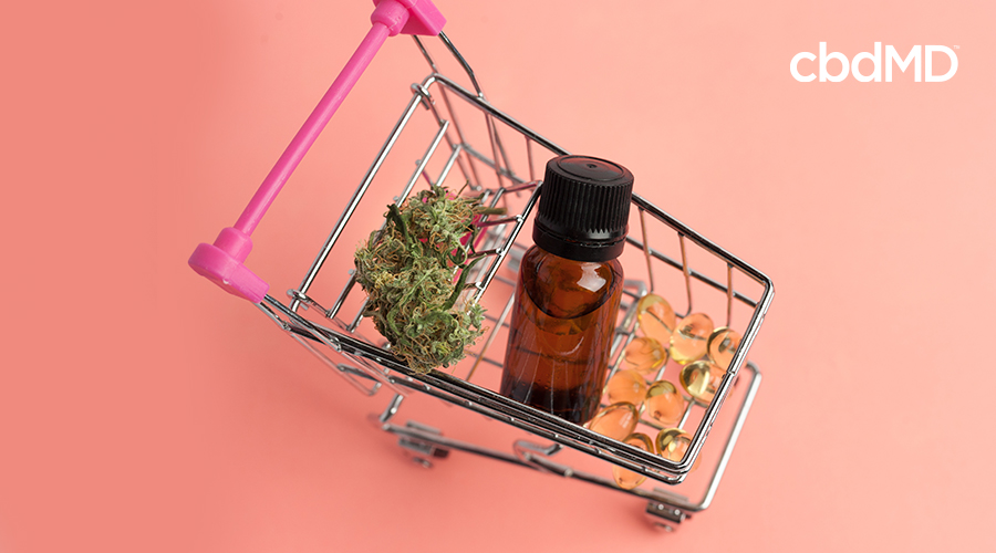 Shopping cart with a cannabis bud, CBD oil bottle, and CBD softgels in it.