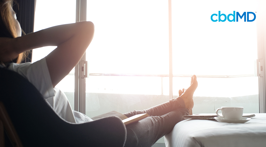 woman relaxing in hotel room with feet up