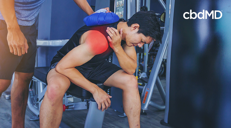 man with icing shoulder in severe pain after working out