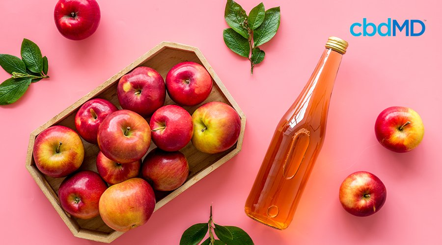 Apples on a tray and a bottle of vinegar next to each other.