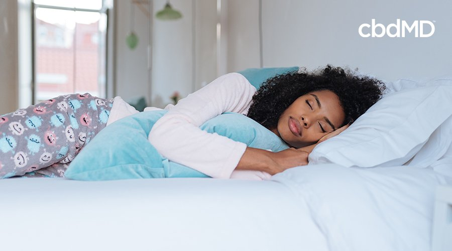 A dark woman sleeps comfortably with a large smile on her face