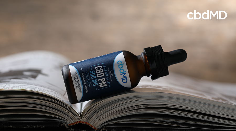 cbdMD pm tincture laying on top of a book