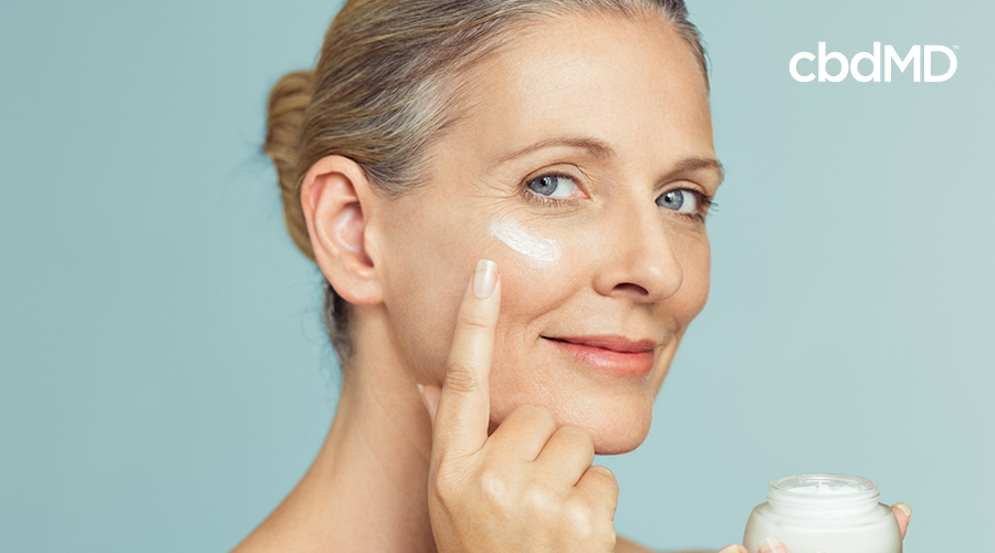 woman applying natural cream to face
