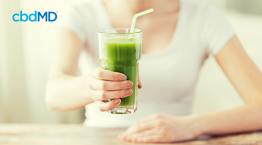 A woman in a white t-shirt reaches out to hand over a glass filled with green juice