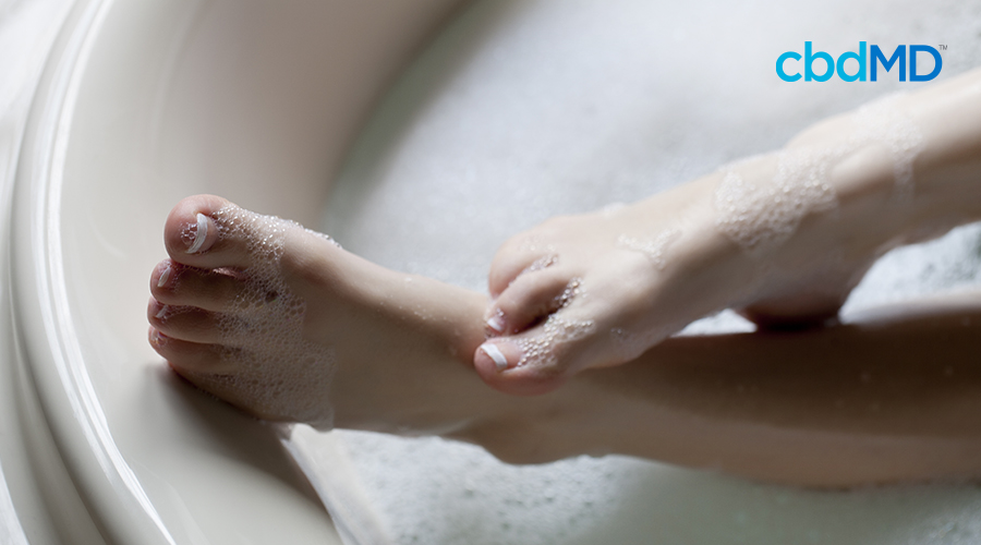 A woman's pedicured feet lifting out of a bubble bath