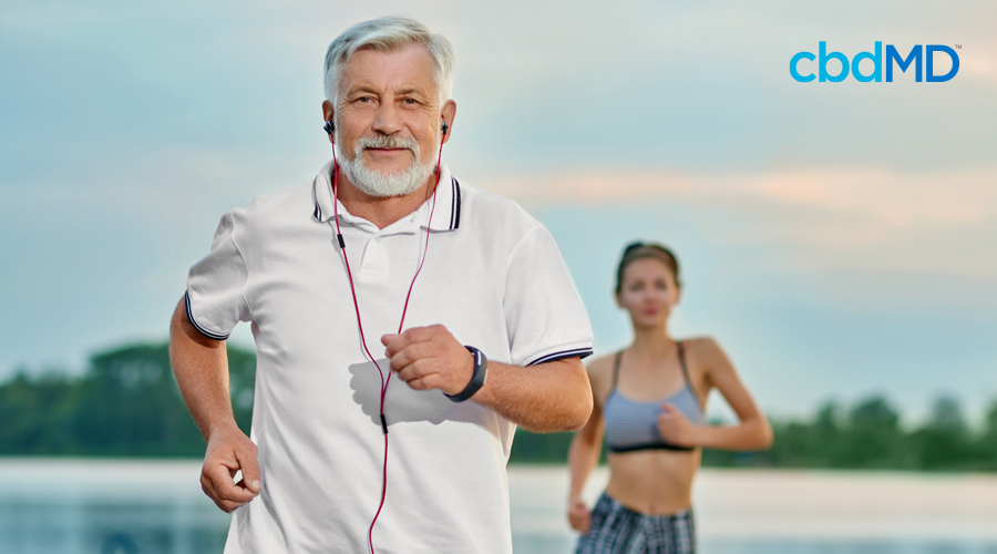 An older gentleman in a white polo shirt, jogs with headphones while an attractive woman follows him in the background