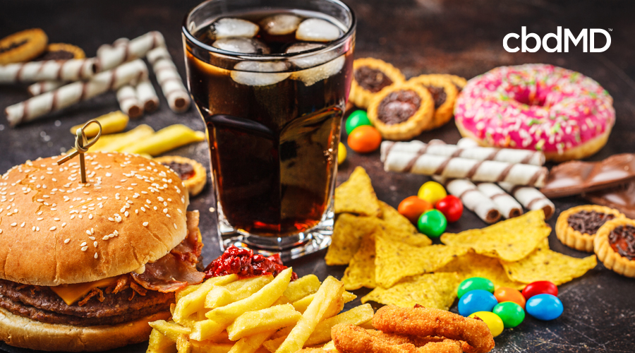 A table is laid out with a variety of junk food, including a glass of soft drink, chips, fries, candy, and a hamburger