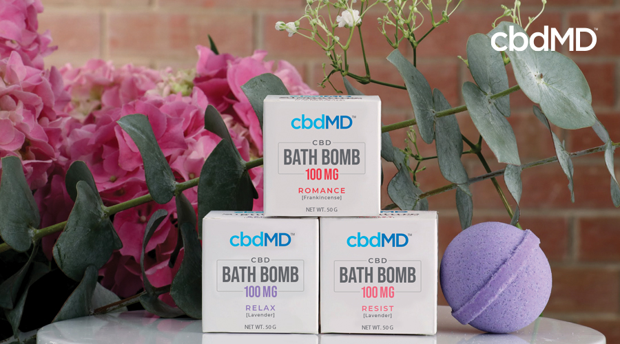 Three Romance, Relax, Resist boxes of CBD bath bombs stacked next to purple Relax lavender bath bomb with pink flowers and plants in background