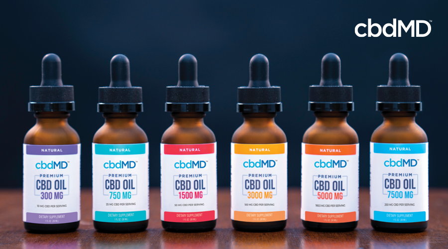 Lineup of six natural flavored cbdMD CBD oil tinctures in different colors with varying strengths of 300 mg, 750 mg, 1500 mg, 3000 mg, 5000 mg, 7500 mg