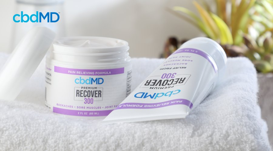 Uncovered tub of cbdMD 300 mg Recover cream next to squeeze tube of 300 mg CBD Recover on white towel with plant in background