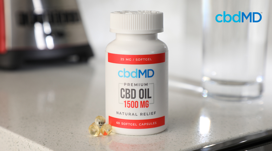 A white bottle of 1500 mg CBD Oil from cbdMD sits on a counter top near an empty glass