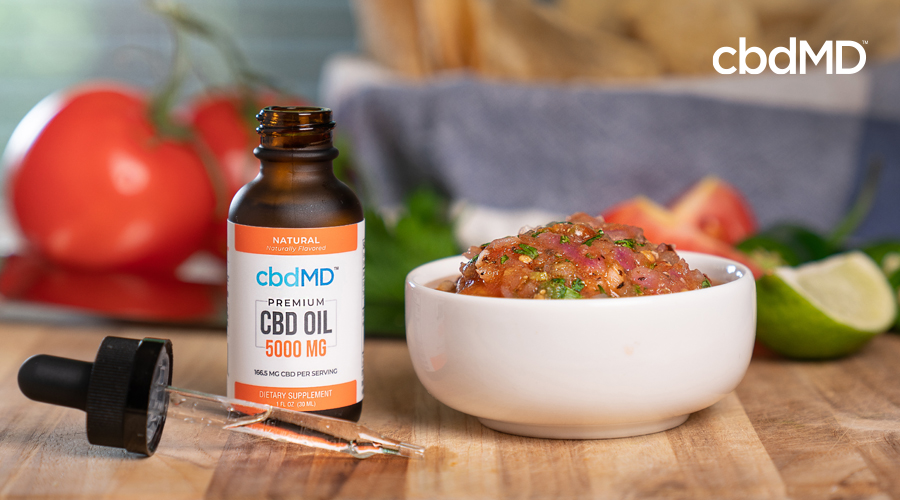 A bottle of 5000 mg CBD Oil from cbdMD sits beside a bowl of pico de gallo