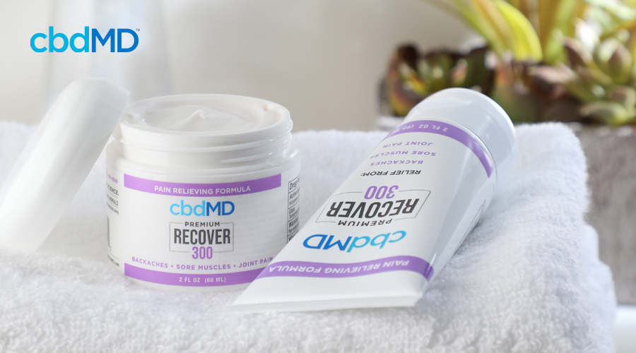 cbdMD's 300 mg CBD Recover tub rests on white towel with top unscrewed sitting next to squeeze bottle of 300 mg CBD Recover laying flat on towel