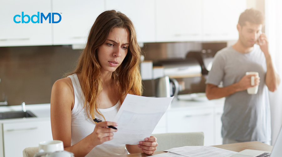 Concerned woman with long brown hair stands and reads letter while holding pen in kitchen with husband in the background on the phone holding cup of coffee