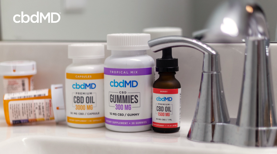 Bottle of 3000 mg CBD oil capsules and 300 mg CBD gummies next to 1500 mg CBD oil tincture by cbdMD on bathroom sink next to faucet and prescription pill bottles
