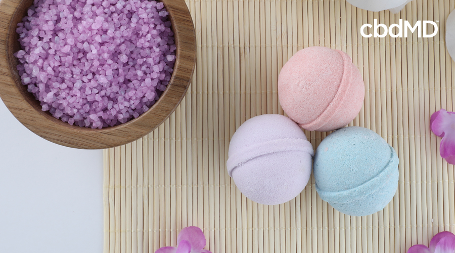 Pink, light blue, and purple CBD bath bombs rest on wood placemat with purple flowers scattered and wooden bowl of purple epsom salt