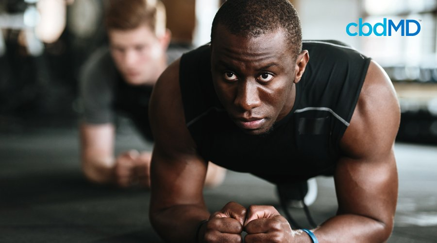 Man in black sleeveless workout shirt holding plank position with man in gray shirt doing plank in background at gym