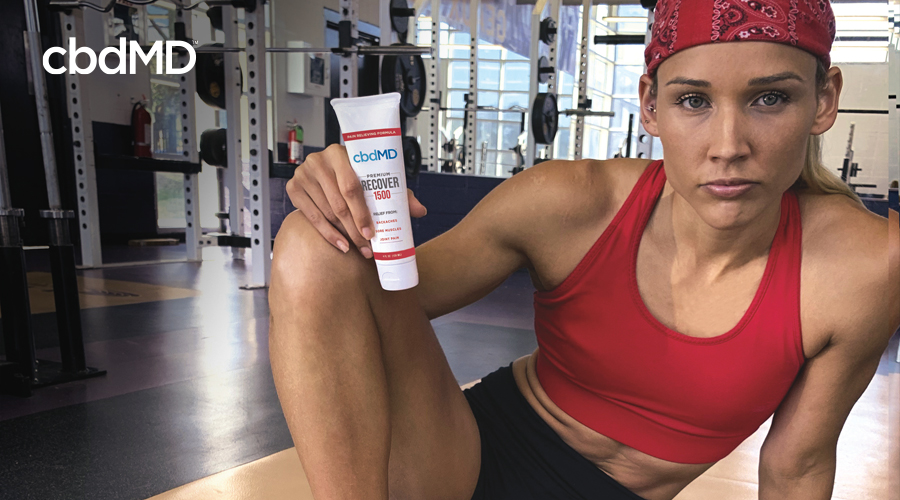 bdMD Athlete Lolo Jones in red top and bandanna with black shorts in gym with squeeze tube bottle of 1500 CBD Recover topical resting on right knee