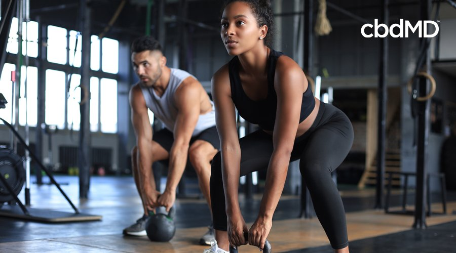 Dark-haired woman in black workout pants and tee squats with kettlebell in gym with man in gray shirt squatting with kettlebell in background