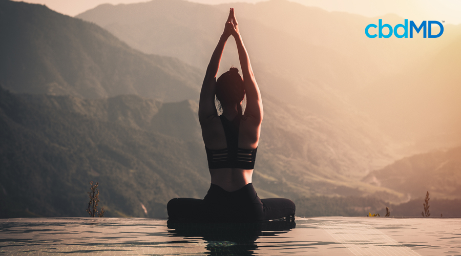 Woman sits in yoga pose with hands extended above her head on edge of water with mountain landscape in the background