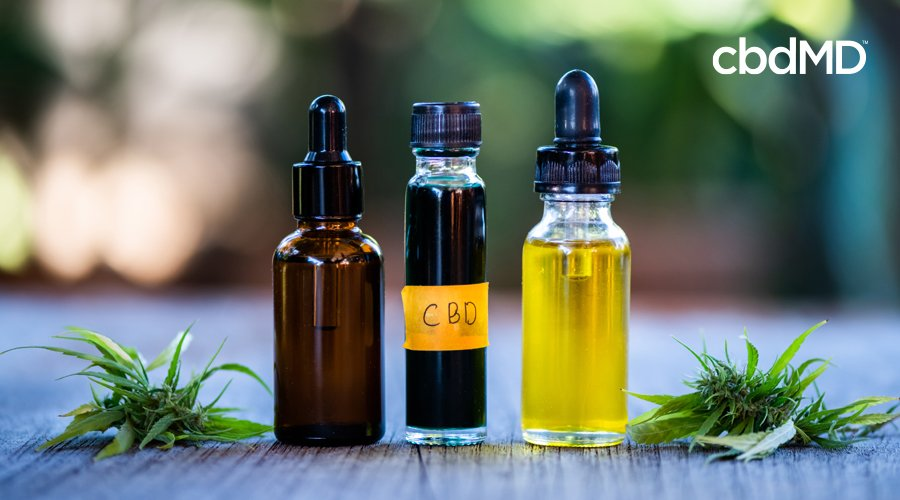 A clear bottle of CBD oil sits between a brown glass dropper bottle and a clear glass dropper bottle on a wooden table