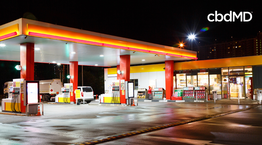 A gas station and attached convenience store brightly lit at night