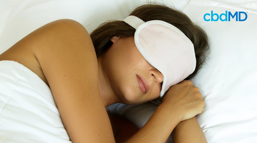 Dark-haired woman rests peaceful in bed with white sheets and white sleep mask covering eyes