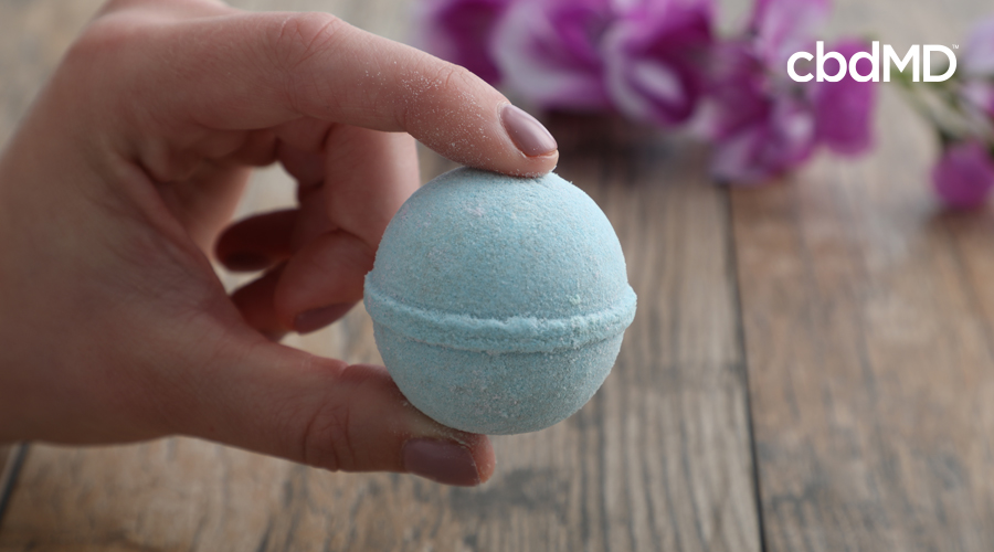 Manicured hand holds single eucalyptus Rejuvenation CBD bath bomb above wooden table with purple flowers in background