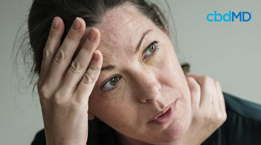 Dark-haired woman appears stressed with hands on forehead and rubbing neck