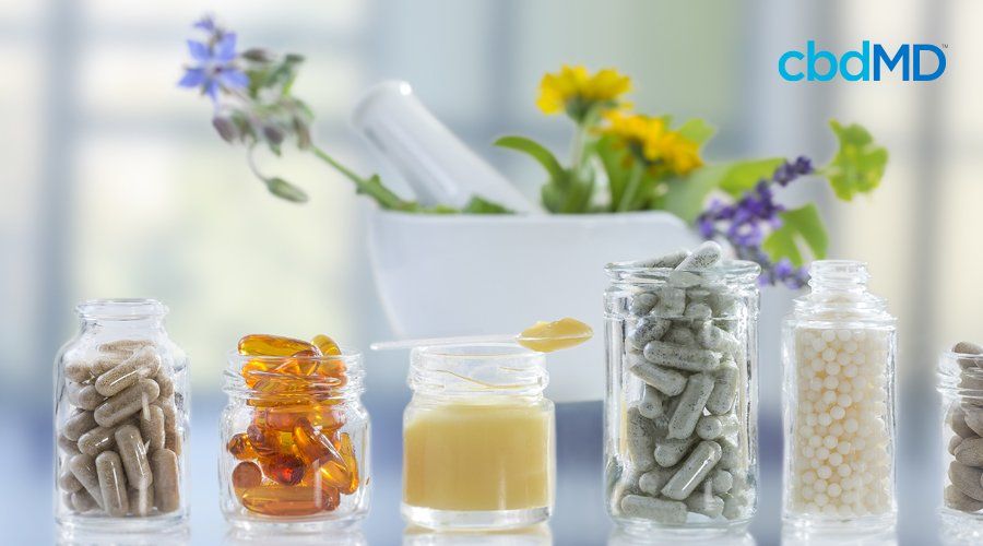 six jars filled with capsules, softgels, lotion, bead balls with mortar and pestle in background filled with variety of yellow, purple, blue flowers