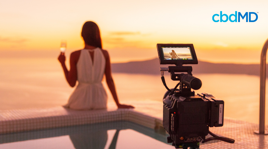 Dark-haired woman sits on the edge of a pool with a glass of wine in the background with video camera resting in the foreground