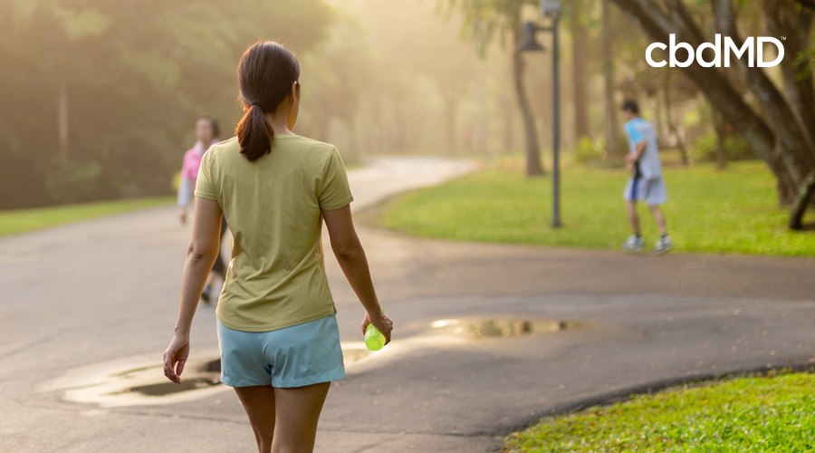 Dark-haired woman in ponytail walks down street with water bottle in hand wearing light yellow shirt and light blue shorts with man running and woman walking in background