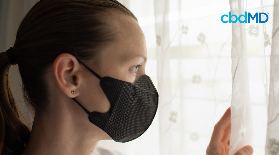 ark-haired woman in ponytail looks out of window with black face mask on